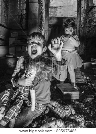 Photo of creepy young children standing over old dolls and in a barn covered in spiderwebs and dust.