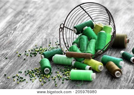 Composition with green sewing threads, beads and metal basket on wooden table