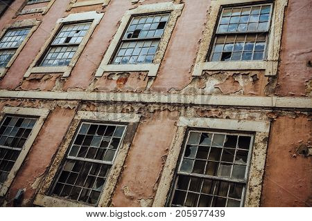 Photo of an old broken building exterior with busted windows and peeling paint.