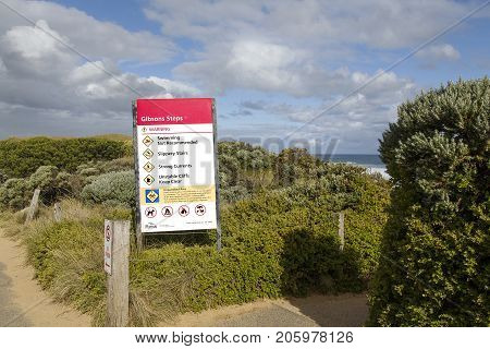 Melbourne, Australia: April 02, 2017: Victoria Parks location and warning sign leading to Gibson's Steps on the Great Ocean Road near the Twelve Apostles Sea Rocks warning of the dangers on the cliffs and strong currents