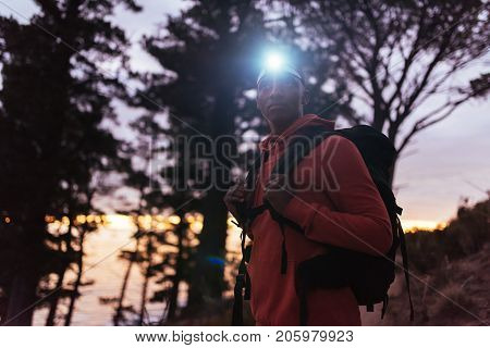 Young African man wearing a headlamp standing alone in the woods while out for a cross country run at dusk