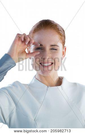 Portrait of smiling woman adjusting imaginary eyeglasses against white background