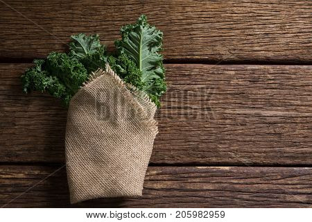 Overhead of wrapped mustard greens on wooden table