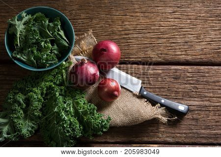 Overhead of mustard greens and onions on wooden table