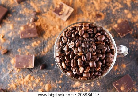 Full Glass Cup Of Roasted Coffee Beans On The Dark Stone Background With Dissipate Cocoa, Pieces Of