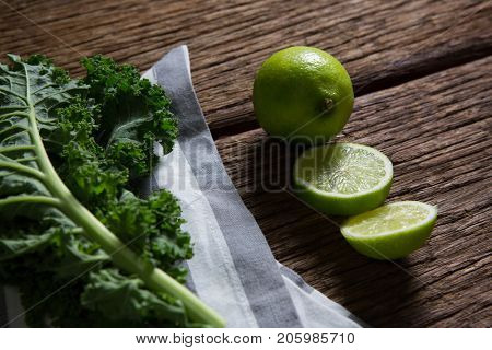 Close-up of mustard greens and lemon on wooden table