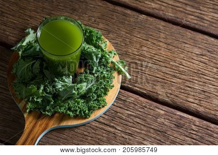 Overhead of mustard greens and juice on wooden board