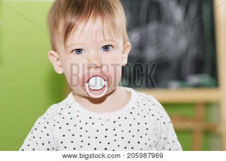 Portrait Of A Beautiful Baby With Pacifier In The Mouth