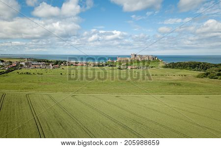 An elevated drone view of Bamburgh Village and Castle on a bright summers day with arable farmland in the foreground and the North Sea behind.