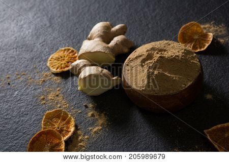 Bowl of ginger powder with ginger and dried lemon on black background