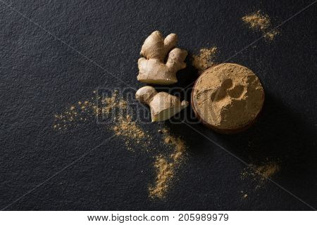 Bowl of ginger powder with ginger on black background