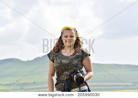 pretty female photographer outdoors. Outdoor summer smiling lifestyle portrait of pretty young woman