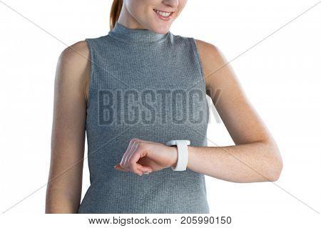 Mid section of businesswoman looking at wrist watch while standing against white background