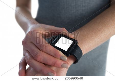 Mid section of businesswoman adjusting smart watch while standing against white background