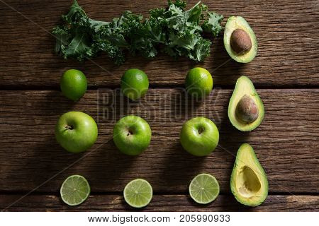 Overhead of mustard greens, lemon, avocado and green apple arranged on wooden table