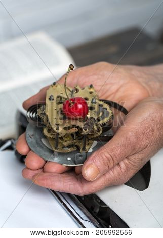 Biomechanics technology food cake on plate of mechanical watches in hands old woman cherry for dessert vitamins nature and technology concept of time and future past and present retro antiques