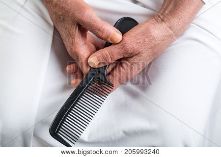 Hairbrush old hands hold comb for hairstyle of mature woman. Woman aged in beauty salon expects hairdresser. Style for pensioner. Beauty women's hands with wrinkles and hair styling care for body