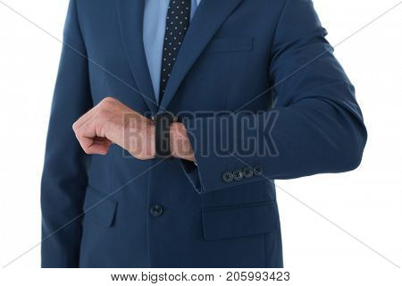 Mid section of businessman wearing wrist watch while standing against white background