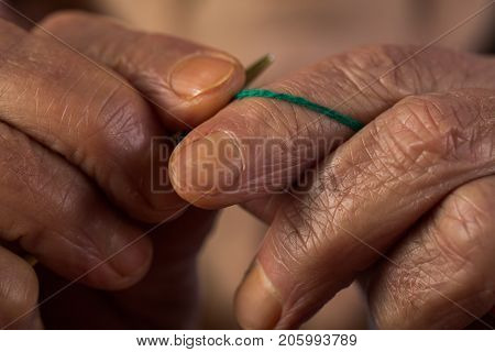 Knitting old hands and fingers holding knitting needle and woolen thread grandmother prepares scarf or sweater hands with wrinkles retired hobbies in retirement memories of grandmother vintage
