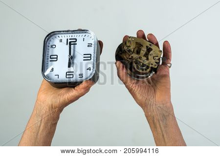 Time concept clock alarm clock watch mechanism old and new watches. Old female hands hold the dial. Hours and minutes age old age and changes. Figures on the dial working hours. Deadline