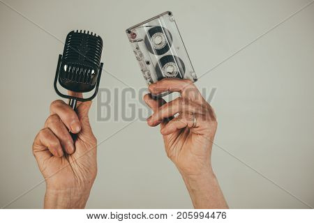 Retro music cassette and microphone in hands of old woman retro sound recording technique. Music of previous generations. Obsolete equipment antique musical technology. Aged mature music lover