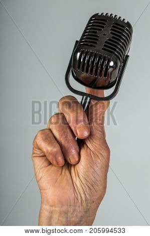 Microphone retro in hand of old woman. Elderly woman's hand holds microphone for singer or appearances in public at protest rally demonstration at conference. Old woman's voice age problems