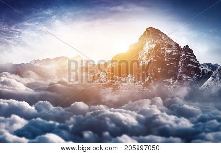 A majestic, snow capped mountain peak towers above the cloud tops as bright, warm light illuminates the scene.