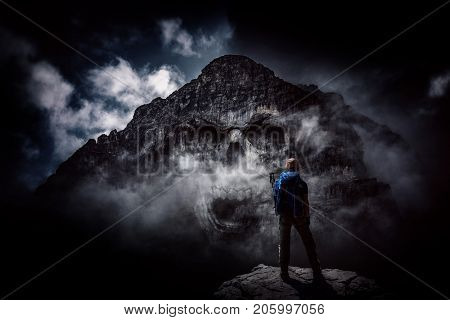 A mountaineer standing in a dark, scary scene with an evil mountain skull face.