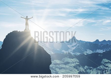A triumphant mountaineer standing on a pinnacle embraces the bright morning sun light with outstretched arms in a majestic mountain scene.