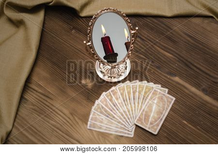 Tarot cards mirror with reflection of candle on wooden table. Fortune teller. Paranormal desk table.