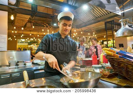 SAINT PETERSBURG, RUSSIA - CIRCA AUGUST, 2017: man expertly prepare the food in wok at Marketplace restaurant.