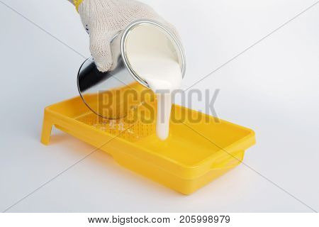 Pouring white paint into a painting tray