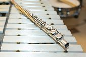 symphonic and brass band, percussion and wind instrument concept - beautiful closeup on western concert flute lies on beige bars of xylophone, orchestra, ensembles, jazz concerts, selective focus poster