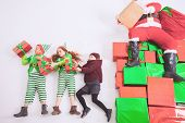 Santa's helpers are working at North Pole, elves and kids holding gift boxes. Merry Christmas. Santa sitting at many gift boxes and reading wishes list. Letters To Santa Claus. Wish list. Black Friday poster