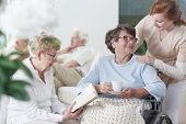 Two elder ladies in glasses spending time together in common room of nursing home poster