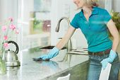 Professional house cleaning service concept smiling woman wiping down marble kitchen countertop using domestic cleaner cloth and rubber household gloves poster