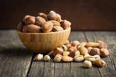 Different types of nuts in the nutshell. Hazelnuts, walnuts, almonds, pecan nuts and pistachio nuts in wooden bowl. poster