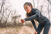Sport watch run woman checking smartwatch tracker. Trail running runner girl looking at heart rate monitor smart watch in forest wearing jacket sportswear. Female athlete jogger training in woods. poster