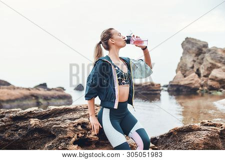 Drink More Water. Sporty Young Woman In Sportswear Drinking Water After Workout While Sitting On The