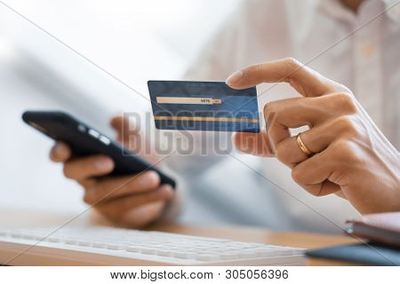 Hand Of Man In Casual Shirt Paying With Credit Card And Using Smart Phone For Online Shopping Making