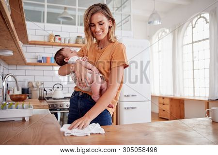 Multi-Tasking Mother Holds Sleeping Baby Son And Cleans In Kitchen