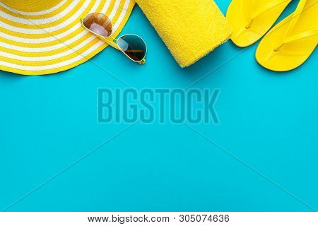 Yellow Summer Beach Accessories On Turquoise Blue Background - Sunglasses, Towel. Flip-flops And Str