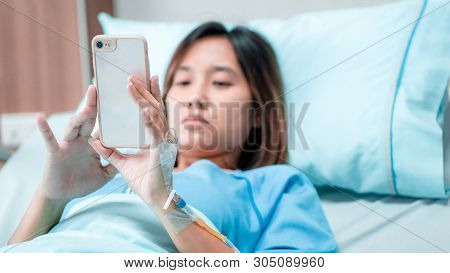 Illness Asia Patient Women And Hospital Concept - Illness Asian Patient Women Using Mobile Phone For
