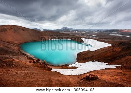 Drammatic view of the lake with turquoise water in vulkano crater. Geothermal valley Leirhnjukur, Myvatn lake, Krafla, Iceland. Famous tourist attraction