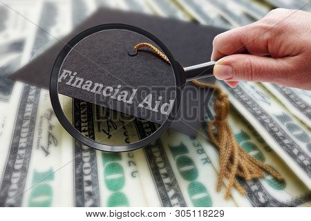Magnifying Glass With Financial Aid Graduation Mortar Board Cap On Money