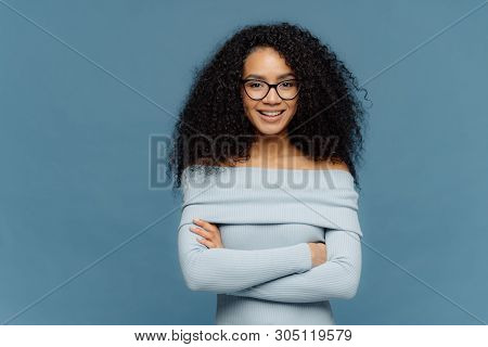Half Length Shot Of Glad Young Female Has Confident Facial Expression, Keeps Arms Folded, Dressed In