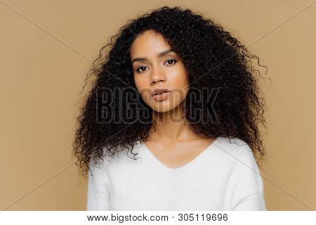 Portrait Of Serious Beautiful Dark Skinned Female With Frizzy Black Hair, Has Minimal Makeup, Looks