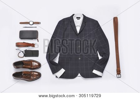 set of classic men`s clothes such as blue suit, brown shoes, belt, watches and bracelet ,cell phone on white background. Flat lay