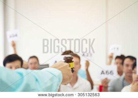 Close Up Auctioneer Hand, Holding Gavel, Wooden Hammer, And Blur Group Of People In Auction Room, On