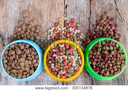 Dry Dog And Cat Food In Bowl Against On Wooden Background